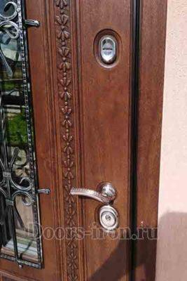 Входная дверь в коттедж со стеклом и ковкой