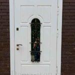 Белая входная дверь с ковкой и стеклом