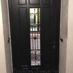 Черная входная дверь с прямоугольным стеклопакетом и кованой решеткой