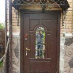 Коричневая входная дверь с отбойником, зеркальной вставкой и ковкой
